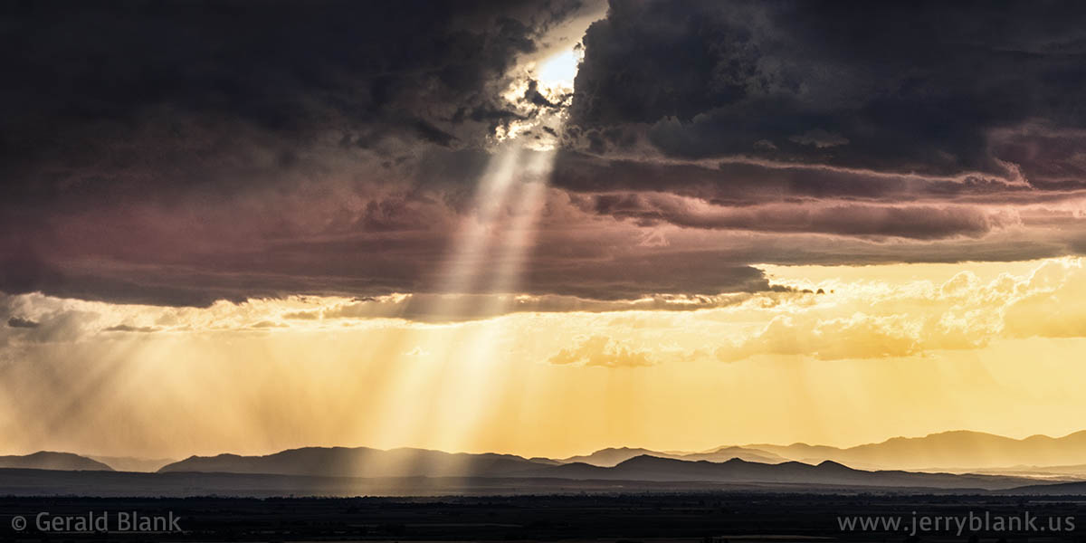 #10196 - Rays of sunlight pierce a storm cloud above the Gallatin Valley in western Montana - photo by Jerry Blank